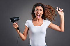 Jeune femme avec un hairdryer Photographie stock libre de droits