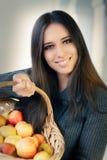 Jeune femme avec un panier des pommes mûres Images stock