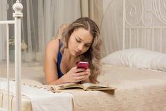 Jeune femme avec un smartphone et un livre Photo stock