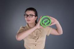 Jeune femme avec @ un symbole Image stock