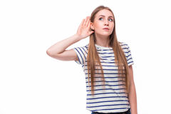 Jeune femme avec un trouble de l'audition ou une perte d'audition mettant en forme de tasse sa main derrière son oreille avec ell photos stock