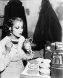 Jeune femme avec une brosse de composer regardant son visage dans un miroir de main (toutes les personnes représentées ne sont pa Photographie stock libre de droits