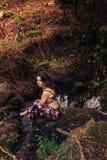 Jeune femme avec une robe intéressante se reposant sur une roche en rivière photos stock