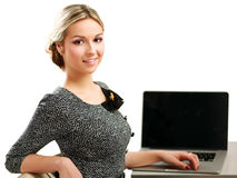 Jeune femme avec une séance d'ordinateur portable d'isolement dessus Photographie stock