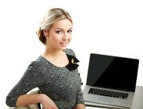 Jeune femme avec une séance d'ordinateur portable d'isolement dessus Images stock