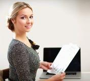 Jeune femme avec une séance d'ordinateur portable d'isolement dessus Photo libre de droits