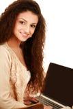 Jeune femme avec une séance d'ordinateur portable d'isolement dessus Photo stock