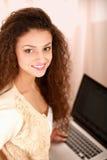 Jeune femme avec une séance d'ordinateur portable d'isolement dessus Images libres de droits