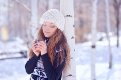 Jeune femme avec une tasse de boisson chaude en parc d'hiver Photo libre de droits
