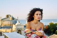 Jeune femme avec une tasse de café dehors photographie stock libre de droits