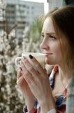 Jeune femme avec une tasse de thé sur le balcon, arbres de fleur sur le fond Images stock