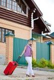 Jeune femme avec une valise rouge Photo stock
