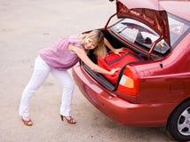 Jeune femme avec une valise rouge dans le véhicule Photographie stock