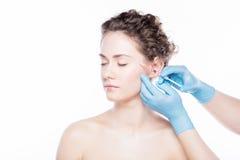 Jeune femme ayant des injections de visage de botox Photographie stock