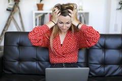 Jeune femme ayant des problèmes avec l'ordinateur portable tout en se reposant sur un divan en cuir image stock