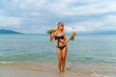 Jeune femme ayant l'amusement avec des ananas sur la plage Photographie stock libre de droits
