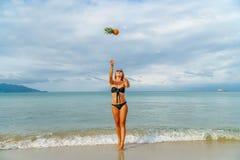Jeune femme ayant l'amusement avec des ananas sur la plage Photo stock