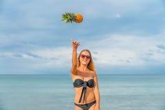 Jeune femme ayant l'amusement avec des ananas sur la plage Image libre de droits