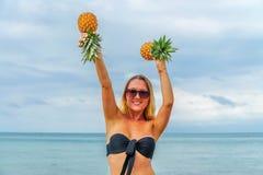Jeune femme ayant l'amusement avec des ananas sur la plage Images stock