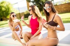 Jeune femme ayant l'amusement et mangeant la pastèque par la piscine Photos stock