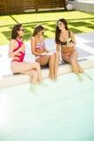 Jeune femme ayant l'amusement par la piscine Photos stock