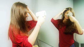 Jeune femme ayant l'amusement séchant de longs cheveux soyeux banque de vidéos