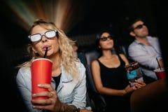 Jeune femme ayant la boisson froide et observant le film 3d Photographie stock libre de droits