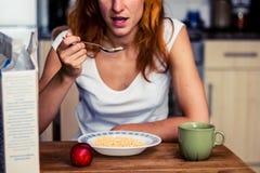 Jeune femme ayant la céréale et le fruit pour le petit déjeuner Photo libre de droits