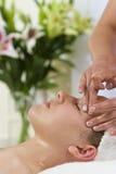 Jeune femme ayant la demande de règlement faciale de massage Image stock
