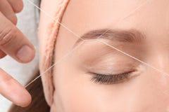 Jeune femme ayant la procédure de correction de sourcil photo stock