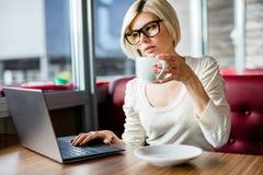 Jeune femme ayant le café tout en travaillant sur l'ordinateur portable en café photographie stock