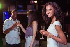 Jeune femme ayant le champagne dans la barre et ses amis grillant des verres Photographie stock