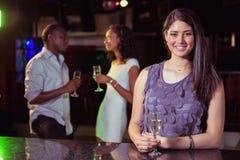 Jeune femme ayant le champagne dans la barre et son parler d'amis Photo stock