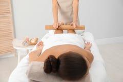 Jeune femme ayant le massage avec le bâton en bambou photo libre de droits