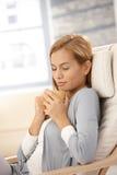 Jeune femme ayant le thé dans le fauteuil Photo stock