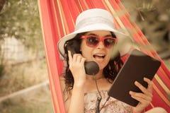 Jeune femme ayant un appel d'Internet et se situant dans l'hamac Image libre de droits