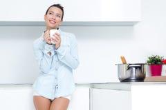 Jeune femme ayant un café à la cuisine Photo stock