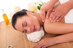 Jeune femme ayant un massage de station thermale sur elle en arrière Photo stock