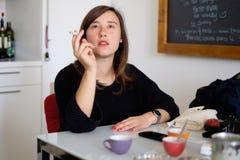 Jeune femme ayant une coupure de café et de cigarette Photographie stock libre de droits