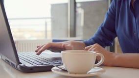 Jeune femme ayant une pause-café, elle remue son expresso et utilise un ordinateur portable, boucle haute de main et sans couture clips vidéos