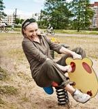 Jeune femme balançant sur une oscillation photo stock
