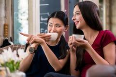 Jeune femme bavarde se dirigeant tout en se reposant dans un café Photographie stock
