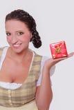 Jeune femme bavaroise dans le dirndl avec un petit cadeau sur votre paume photos stock