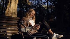 Jeune femme belle dans l'écouteur utilisant son comprimé tout en se reposant sur le banc en parc banque de vidéos