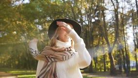 Jeune femme belle dans le chapeau marchant en parc de ville clips vidéos