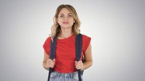 Jeune femme belle dans le T-shirt occasionnel avec le sac à dos et les jeans marchant sur le fond de gradient images libres de droits