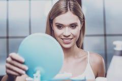 Jeune femme belle mettant un miroir sur l'étagère photos stock
