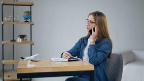 Jeune femme belle parlant au téléphone intelligent à l'agence de voyages banque de vidéos