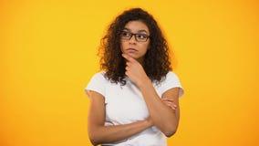 Jeune femme biracial dans des lunettes pensant à la décision, fond jaune banque de vidéos