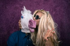 Jeune femme bizarre dans les lunettes de soleil et des oreilles de minou embrassant la licorne heureuse Photo libre de droits